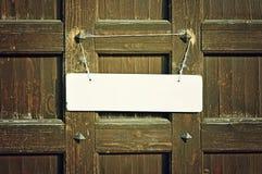 Signe blanc vide accrochant avec la corde déchirée en lambeaux sur le vieux mur en bois brun avec des rivets en métal - rétro fon Photographie stock