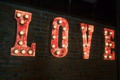 Signe d'ampoule d'AMOUR décoré sur le mur de briques Image libre de droits