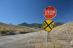 Signe d'arrêt et croisement de chemin de fer ruraux de chemin de terre dans les montagnes Photographie stock