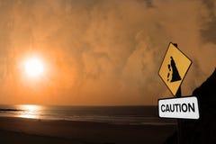 Signe d'attention d'éboulement de plage au coucher du soleil Photographie stock