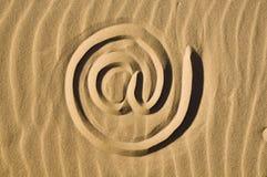 Signe d'email dessiné dans le sable Photographie stock