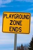 Signe d'extrémité de zone de terrain de jeu contre le ciel nuageux et les arbres bleus Image libre de droits