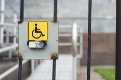 Signe d'incapacité à l'entrée de la porte de fer avec un bouton de cloche sur le fond du passage supérieur équipé photo libre de droits