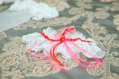 Signe d'infini des anneaux, anneaux de mariage sur un fond blanc, alliances, anneaux de mariage sur un coussin Photos stock