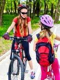 Signe de chemin de bicyclette avec des enfants Filles portant le casque avec le sac à dos Images libres de droits