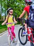 Signe de chemin de bicyclette avec des enfants Filles portant le casque avec le sac à dos Photographie stock