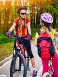 Signe de chemin de bicyclette avec des enfants Filles portant le casque avec le sac à dos Photographie stock libre de droits