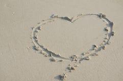 Signe de coeur de l'amour sur le sable à la plage Photographie stock