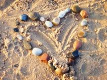 Signe de coeur des pierres Amour, sable et plage en vacances Images libres de droits