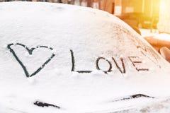 Signe de coeur et inscription d'amour sur un pare-brise de voiture couvert de neige Photographie stock