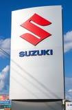 Signe de concessionnaire de Suzuki contre le ciel bleu Photographie stock