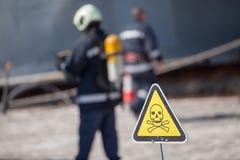 Signe de danger avec le crâne et les os croisés, sapeurs-pompiers sur le fond photo stock