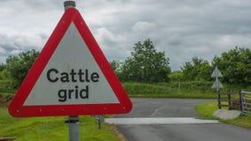 Signe de grille de bétail à côté de grille de bétail Photographie stock