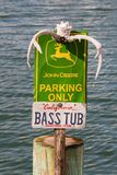 Signe de John Deere Parking Only avec les andouillers de cerfs communs et la plaque minéralogique basse de bateau images stock