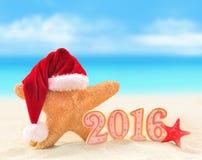 Signe de la nouvelle année 2016 avec des étoiles de mer dans le chapeau de Santa Claus Photo libre de droits