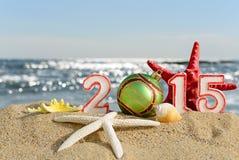 Signe de la nouvelle année 2015 avec la boule de coquillages, d'étoiles de mer et de Noël Image libre de droits