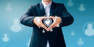 Signe de main d'homme d'affaires au sujet de technologie pour la part d'amour Image libre de droits