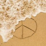 Signe de paix dessiné sur le sable d'une plage avec la vague molle Image stock
