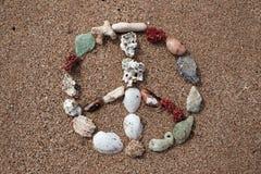 Signe de paix fait avec des coquilles sur la plage d'océan Image libre de droits