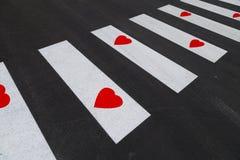 Signe de passage pour piétons avec des symboles rouges de coeur Photographie stock libre de droits