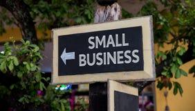 Signe de petite entreprise avec la flèche sur le conseil en bois photos stock
