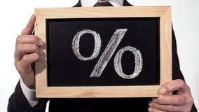 Signe de pour cent dessiné sur le tableau noir dans des mains d'homme d'affaires, taux d'intérêt de dépôt photo libre de droits