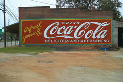 Signe de publicité de Coca Cola de vintage peint du côté du vieux bâtiment en plaines, la Géorgie photographie stock libre de droits