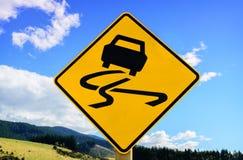 Signe de route glissant jaune photographie stock libre de droits