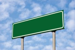 Signe de route vert blanc contre le ciel léger de Cloudscape images stock
