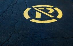 Signe de stationnement interdit peint en jaune sur l'asphalte noir Photographie stock libre de droits