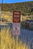 Signe de tête de traînée avec l'avertissement de chien devant l'herbe photographie stock libre de droits