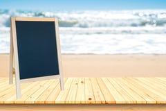 Signe de tableau noir et plate-forme en bois sur la plage et le ciel bleu, au sujet de Photos stock