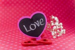 Signe de tableau qui indique l'amour avec des fleurs et a senti des coeurs sur r Photographie stock libre de droits