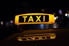 Signe de taxi la nuit, voitures de taxi Photographie stock