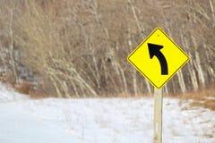 Signe de virage à gauche en avant le long d'une route Image stock