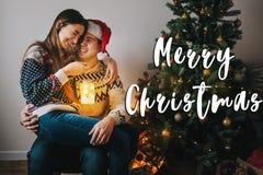 Signe des textes de Joyeux Noël, carte de voeux couples élégants dans le swea Images stock