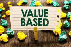 Signe des textes montrant la valeur basée Photo conceptuelle considérant la valeur de produit en satisfaisant la pince à linge de image stock