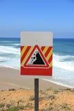 Signe en baisse de roches près d'une plage Photo stock