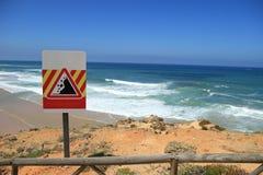 Signe en baisse de roches près d'une plage Photos stock