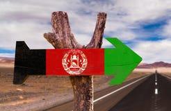 Signe en bois de drapeau de l'Afghanistan avec le fond de route de désert photos libres de droits