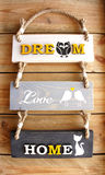 Signe en bois du panneau trois avec le message de ` d'amour de ` de ` de rêve de ` de ` de maison de ` sur le fond en bois photo stock
