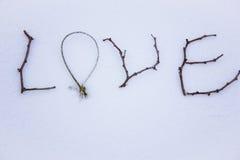 Signe fait de bois dans la neige Jour du ` s de St Valentine Image stock