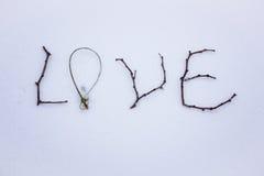 Signe fait de bois dans la neige Jour du ` s de St Valentine coeur en verre rouge sur la neige Photos libres de droits