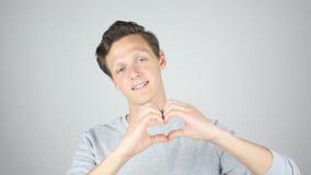 Signe fait main de coeur, jeune homme exprimant l'amour, geste Images libres de droits