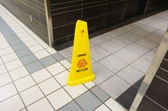 Signe humide glissant de plancher de précaution jaune marqué en anglais et franc Images stock