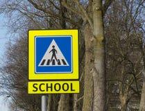Signe jaune de croisement d'école avec des arbres Photo libre de droits