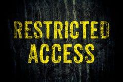 Signe limité de danger d'avertissement d'accès dans les lettres jaunes peintes au-dessus du mur en béton de ciment sale foncé photos stock