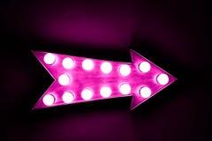 Signe lumineux lumineux et coloré de vintage rose d'affichage de flèche Images stock