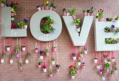 Signe romantique de l'amour avec des fleurs et avec les briques roses à l'arrière-plan Image libre de droits
