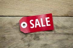 Signe rouge avec la vente sur le fond en bois Photos stock